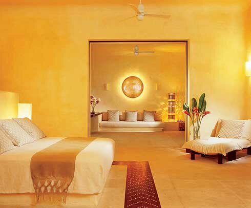 Contemporary-bedroom-with-tiling-floor-and-sand-color-wall-and-lamps-with-bed-cover